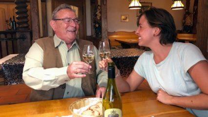 Ein älterer Herr und eine junge Frau stoßen mit Weingläsern an.