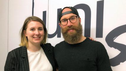 Ein junger Mann und eine junge Frau lächeln in die Kamera.