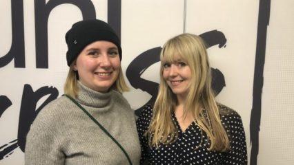Zwei junge Frauen lächeln in die Kamera.