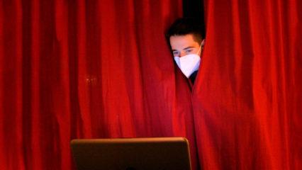 Junger Mann guckt aus Theatervorhang raus