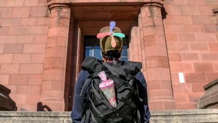 Student mit Schultüte und Propeller-Kappe vor Unigebäude