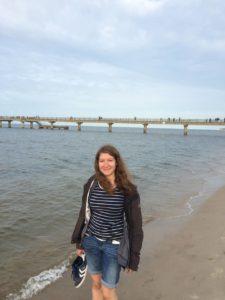Eine Frau läuft am Strand lang.