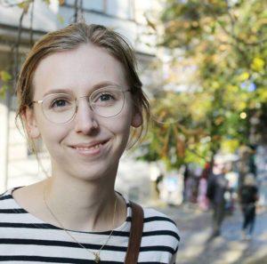 Eine junge Studentin lächelt in die Kamera.