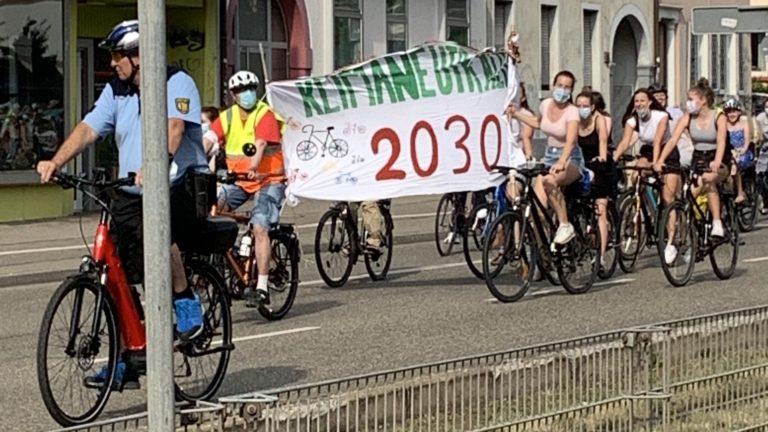 """Fahrradfahrer mit Banner """"Klimaneutralität 2030"""""""